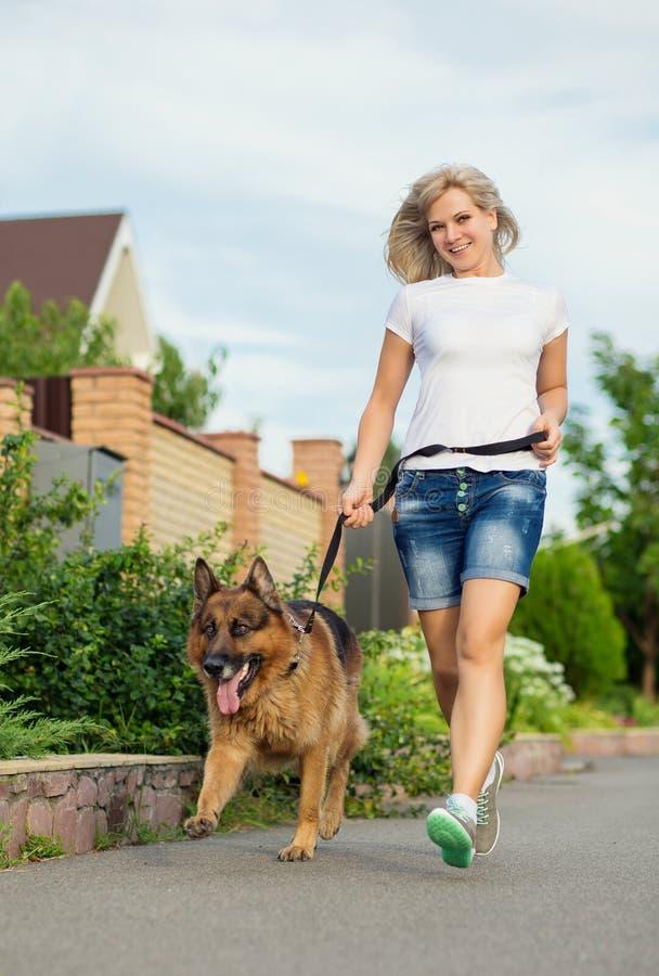 Mujer que corre con su perro foto de archivo