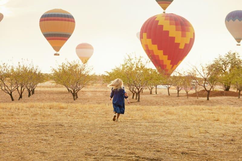 Mujer que corre en campo con el vuelo de los globos del aire caliente imágenes de archivo libres de regalías