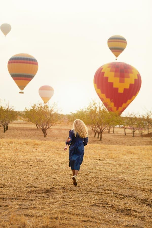 Mujer que corre en campo con el vuelo de los globos del aire caliente fotos de archivo libres de regalías
