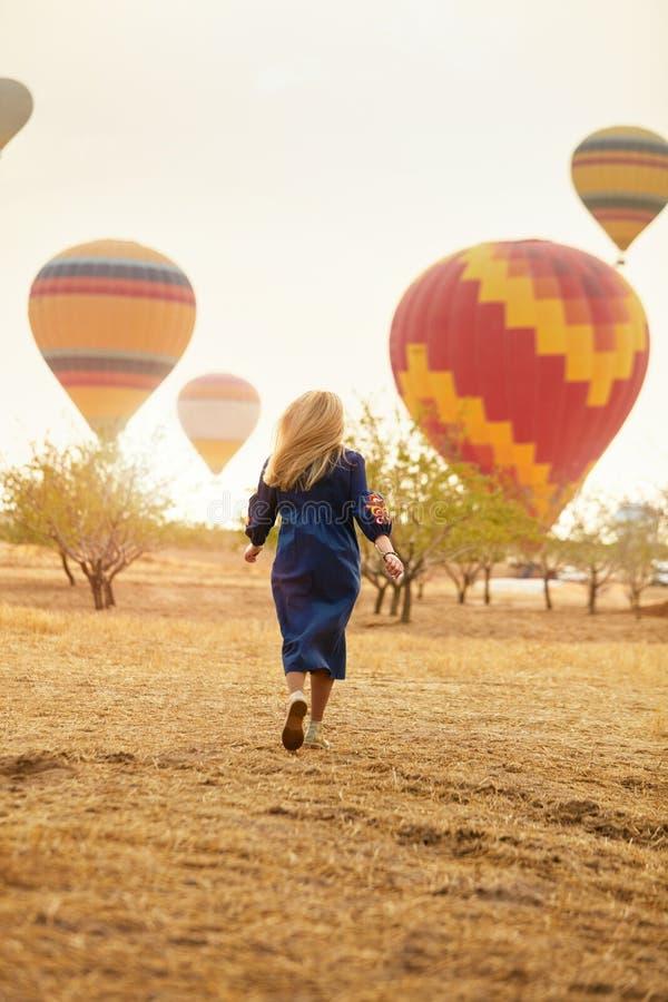 Mujer que corre en campo con el vuelo de los globos del aire caliente imagen de archivo