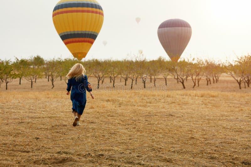Mujer que corre en campo con el vuelo de los globos del aire caliente foto de archivo