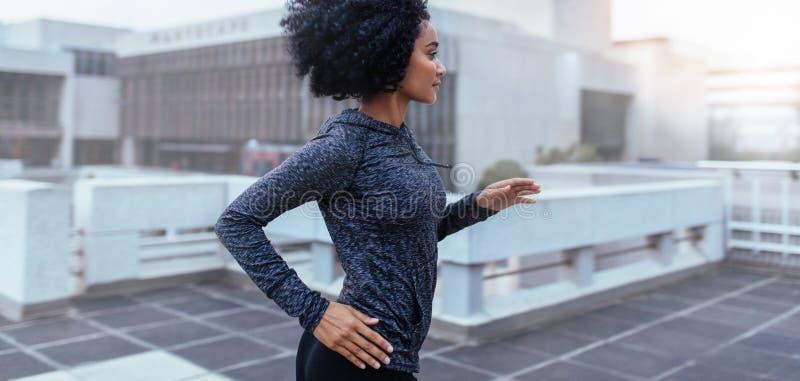 Mujer que corre en la ciudad imagen de archivo
