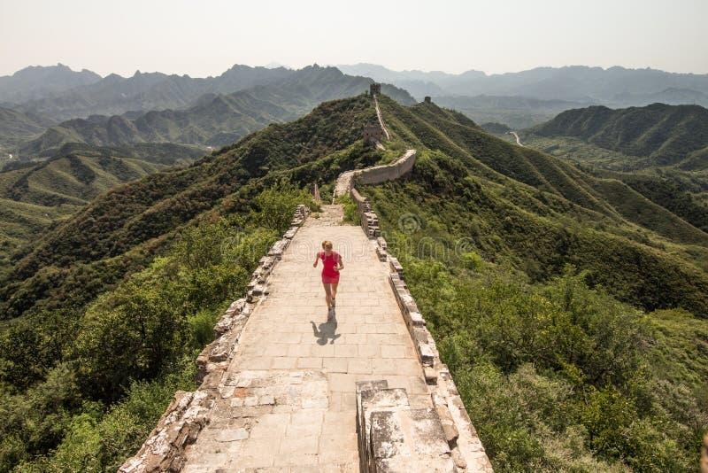 Mujer que corre en la pared china fotografía de archivo