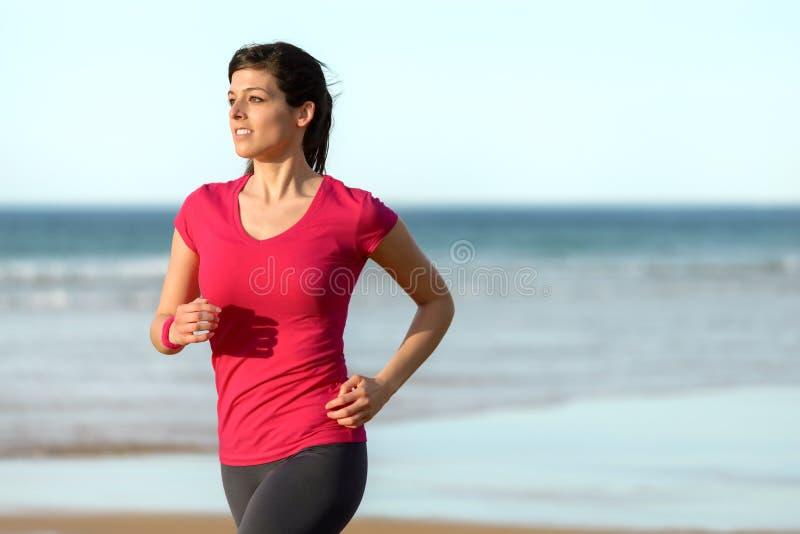 Mujer que corre en la playa fotografía de archivo