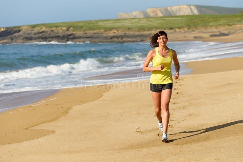 Mujer que corre en la playa de la arena fotografía de archivo