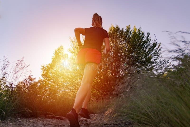 Mujer que corre en las monta?as en la puesta del sol imagen de archivo libre de regalías