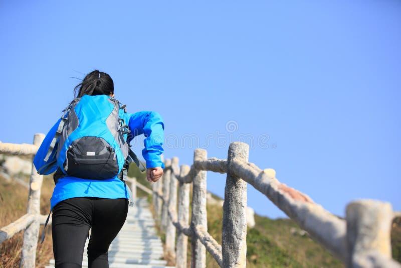 Mujer que corre hasta pico de montaña imágenes de archivo libres de regalías
