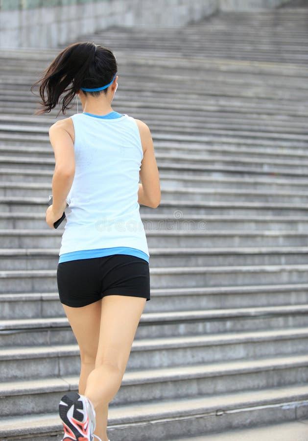 Mujer que corre para arriba en las escaleras de piedra fotografía de archivo