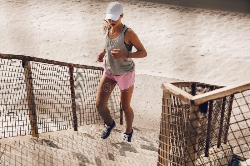 Mujer que corre para arriba la escalera en la playa fotografía de archivo libre de regalías