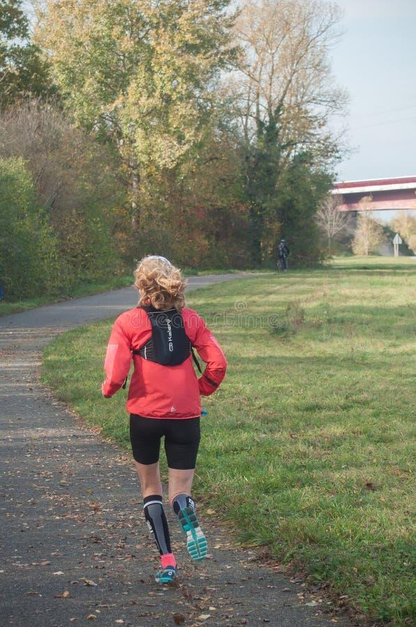 Mujer que corre solamente en el camino en otoño fotos de archivo libres de regalías