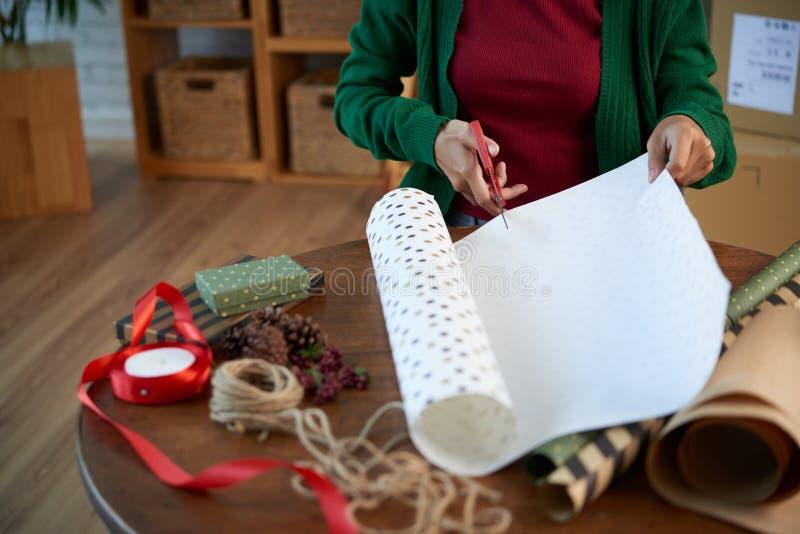 Mujer que corta el papel para envolver el presente fotos de archivo libres de regalías