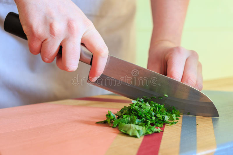 Mujer que corta el perejil fresco con un cuchillo grande en el tablero de madera colorido imágenes de archivo libres de regalías