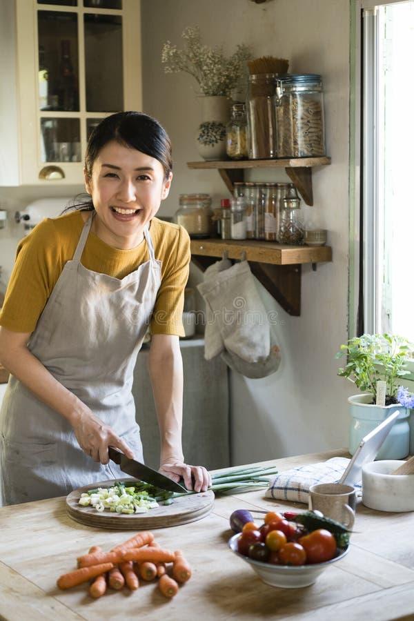 Mujer que corta las cebollas verdes en la cocina foto de archivo