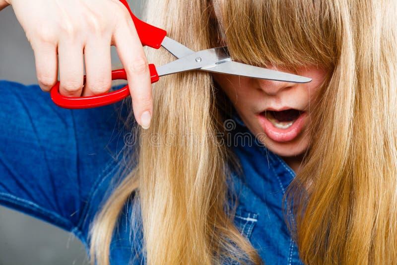 Mujer que corta su franja imágenes de archivo libres de regalías