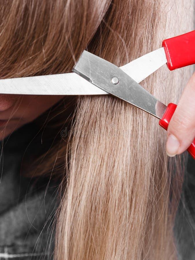 Mujer que corta su franja foto de archivo