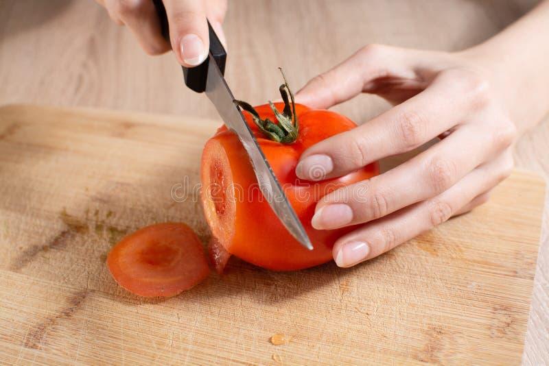 Mujer que corta un tomate en el tablero cortado de madera imagen de archivo libre de regalías