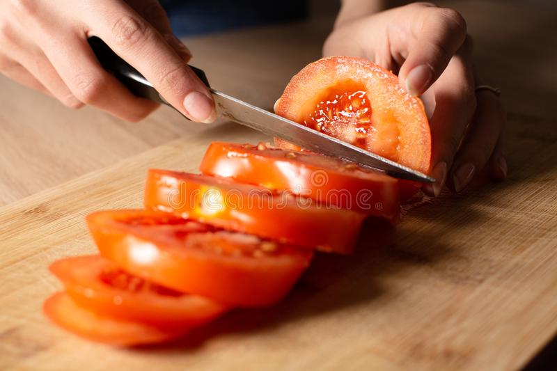 Mujer que corta un tomate en el tablero cortado imagenes de archivo