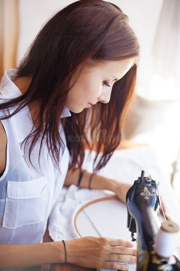 Mujer que cose en la máquina de coser vieja foto de archivo