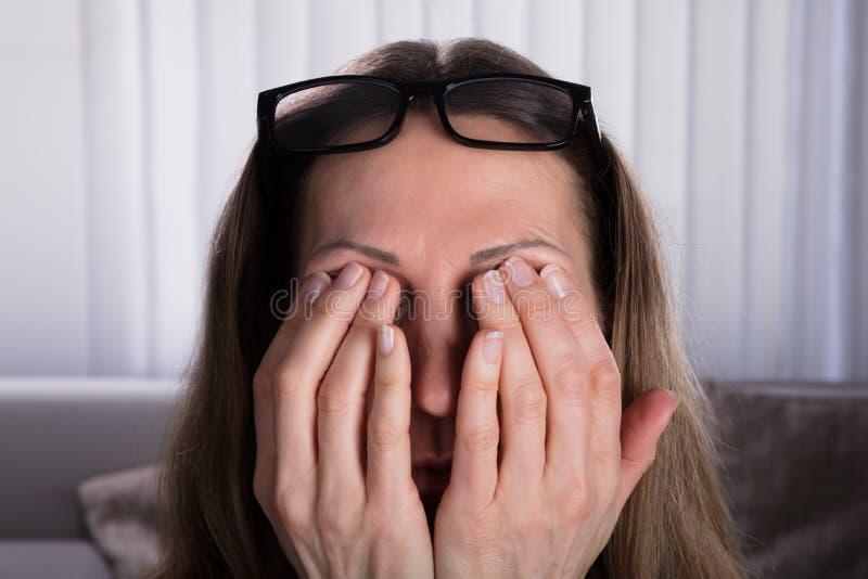 Mujer que cubre sus ojos con las manos imagenes de archivo