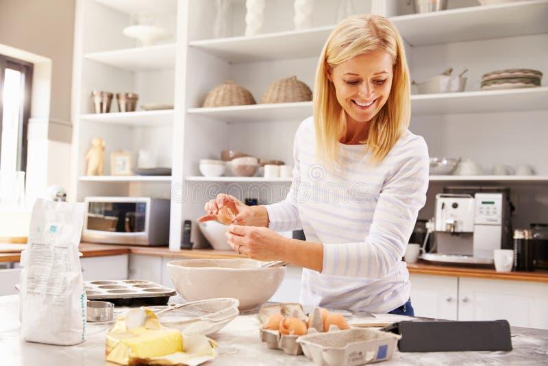 Mujer que cuece en casa receta de siguiente en una tableta imagen de archivo