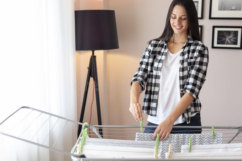 Mujer que cuelga la ropa lavada mojada en un estante de sequía imagen de archivo libre de regalías