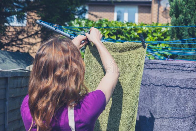 Mujer que cuelga su lavadero en jardín imagen de archivo