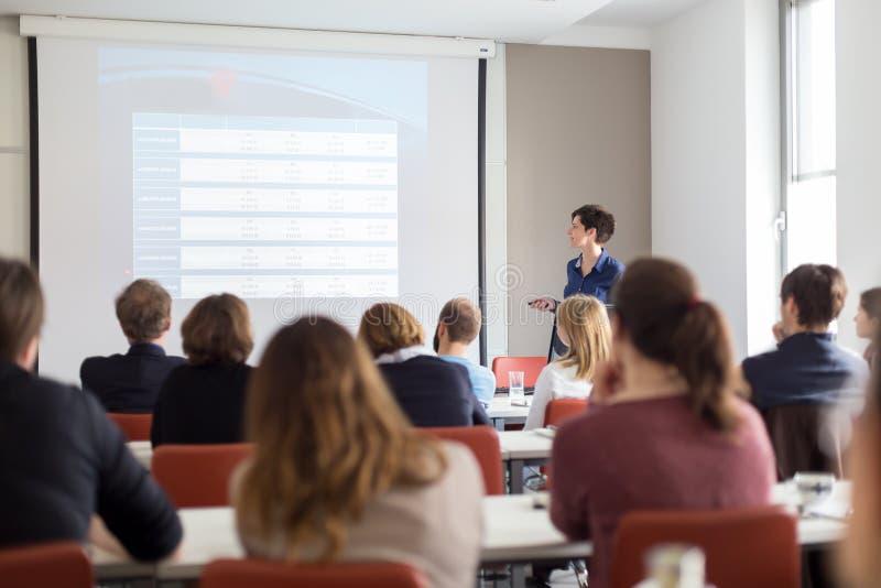 Mujer que da la presentación en sala de conferencias en la universidad