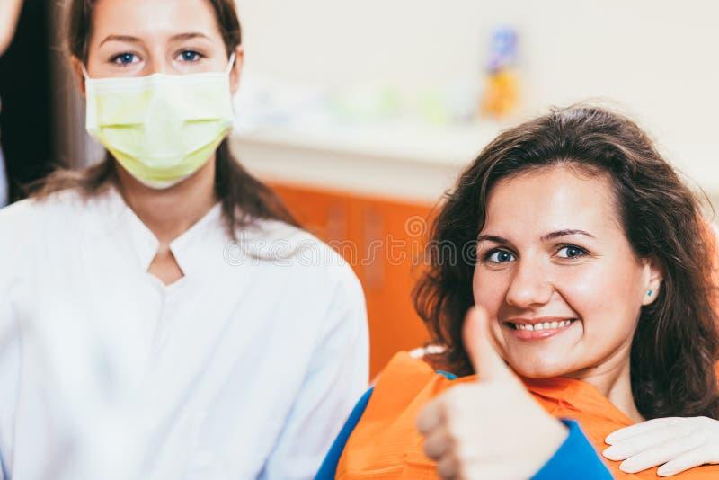 Mujer que da los pulgares para arriba en la oficina del dentista imagen de archivo libre de regalías
