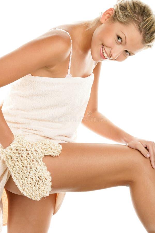 Mujer que da masajes a la pierna con el guante del sisal imagenes de archivo