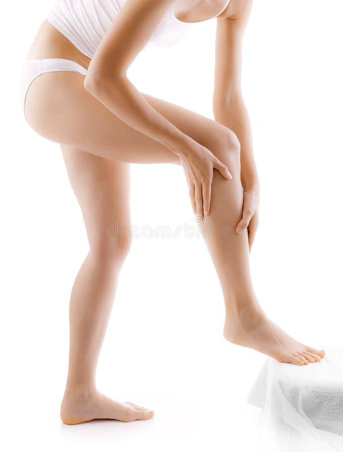 Mujer que da masajes a sus piernas foto de archivo libre de regalías
