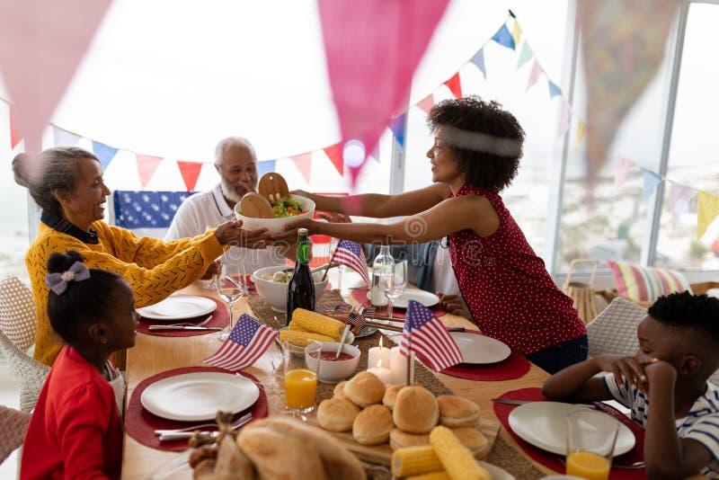 Mujer que da un cuenco de comida para mimar en una mesa de comedor imágenes de archivo libres de regalías