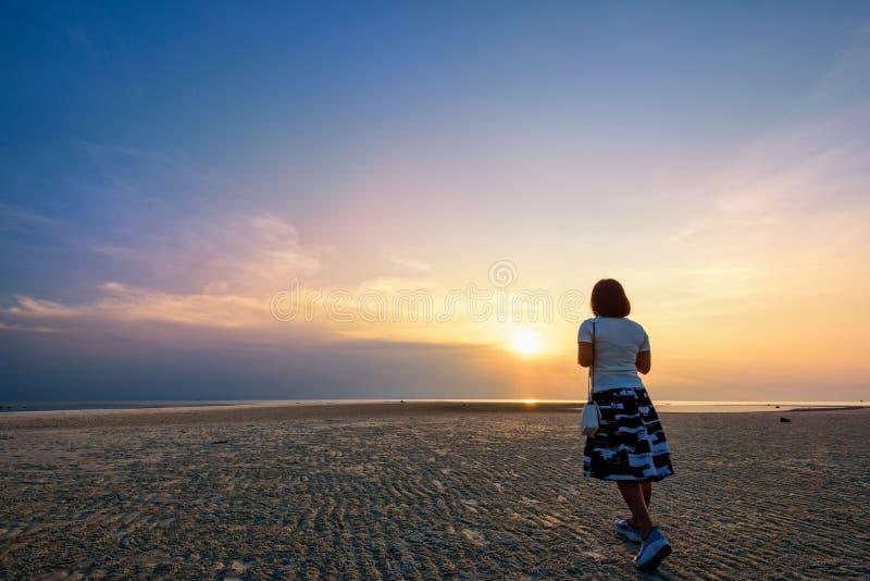 Mujer que da un paseo en la playa en la puesta del sol foto de archivo