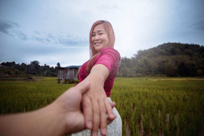 Mujer que da vuelta y que sonríe mientras que lleva a cabo su mano de la mano fotos de archivo