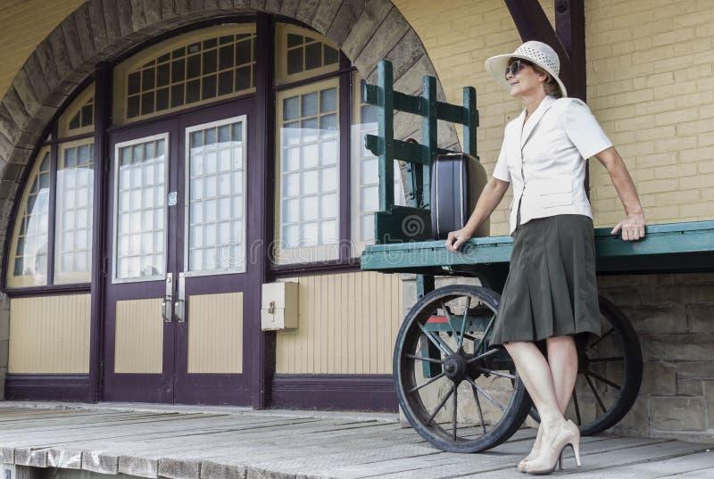 Mujer que defiende y que se inclina contra un carro retro viejo del equipaje la puerta de entrada de la estación de tren imágenes de archivo libres de regalías