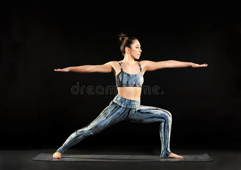 Mujer que demuestra la actitud del guerrero 2 en yoga fotografía de archivo libre de regalías
