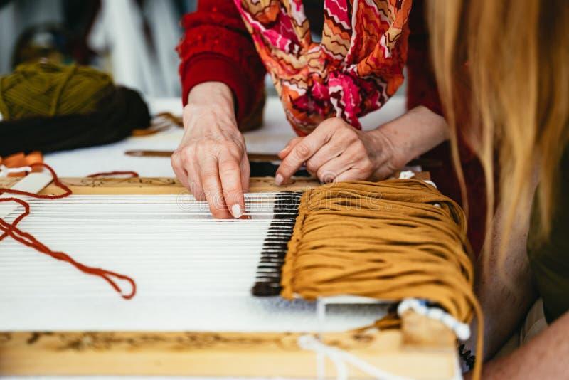 Mujer que demuestra tejer en un telar de mano foto de archivo libre de regalías