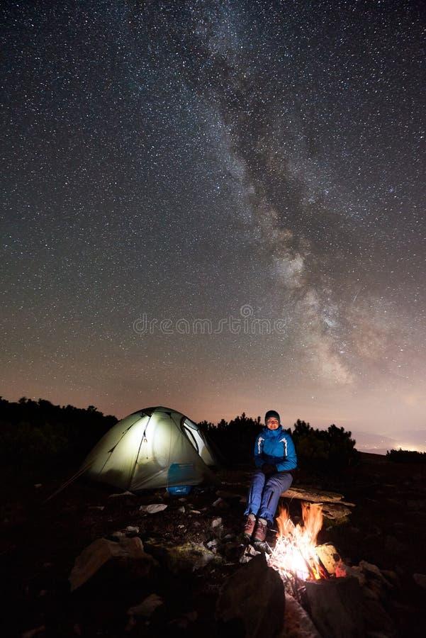 Mujer que descansa en el campo de la noche debajo del cielo estrellado en monta?as foto de archivo libre de regalías