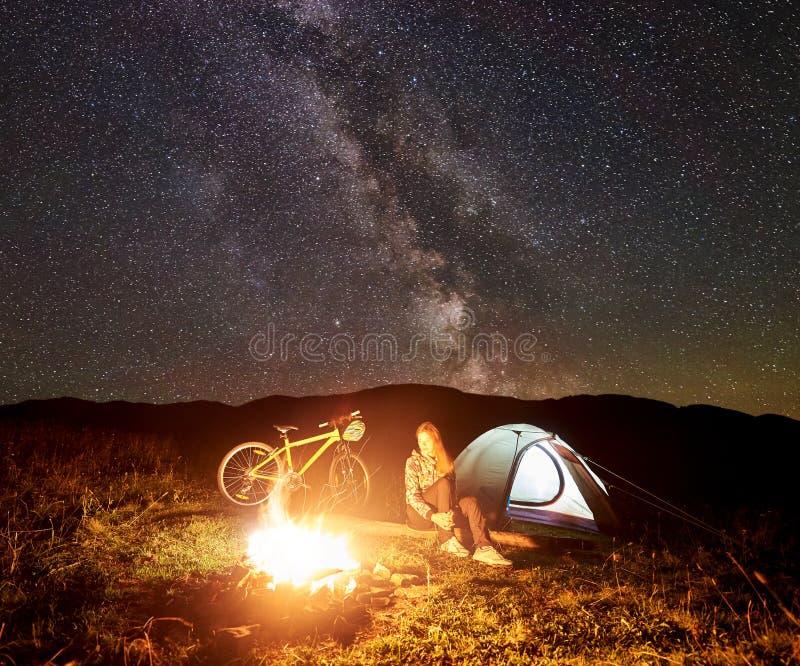 Mujer que descansa en la noche que acampa cerca de la hoguera, tienda tur?stica, bicicleta debajo del cielo de la tarde por compl foto de archivo libre de regalías