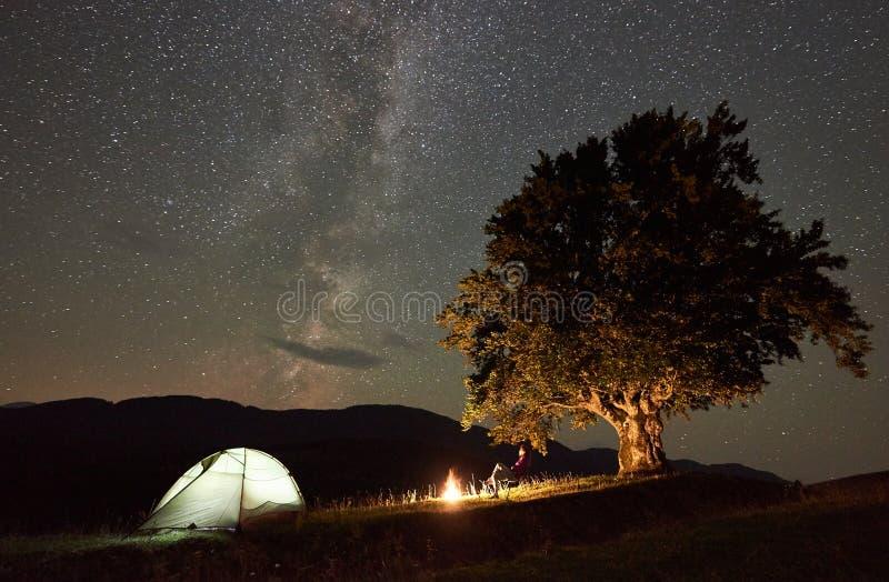 Mujer que descansa en la noche que acampa en monta?as debajo del cielo estrellado imagen de archivo