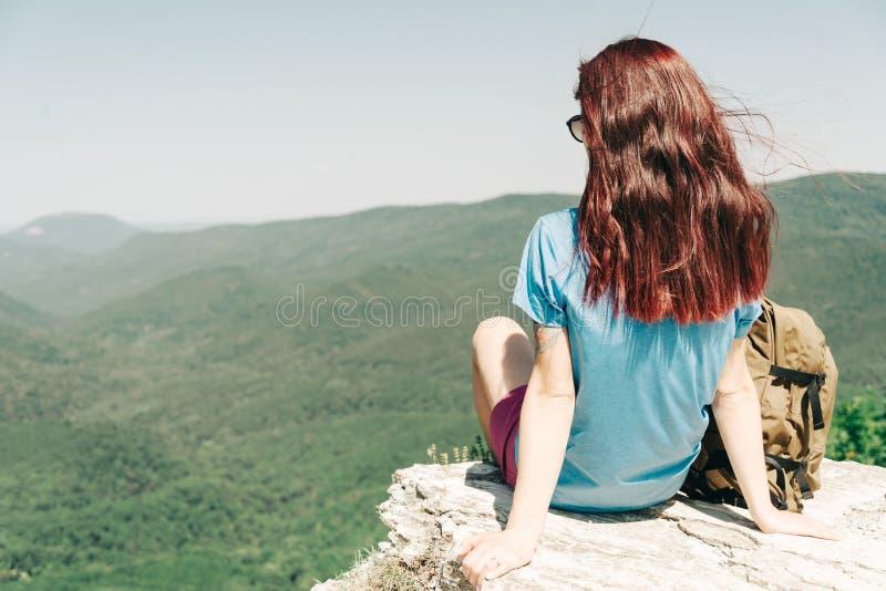 Mujer que descansa encima de la roca alta en montañas imagenes de archivo