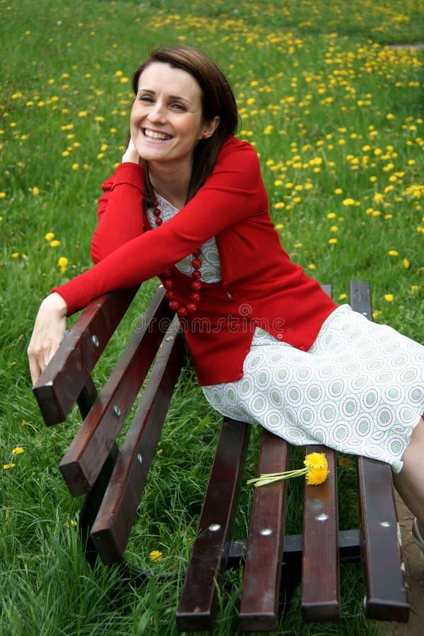 Mujer que descansa sobre banco imágenes de archivo libres de regalías