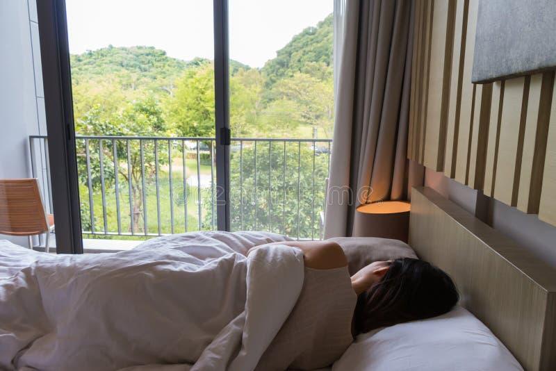 Mujer que descansa sobre la cama y que mira la naturaleza hermosa imagenes de archivo