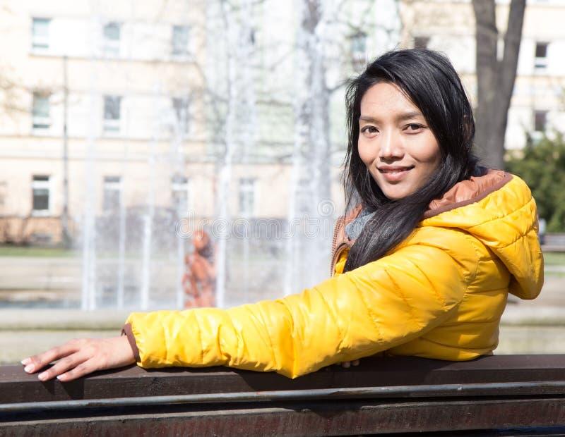 Mujer que descansa sobre un banco en el parque fotos de archivo libres de regalías