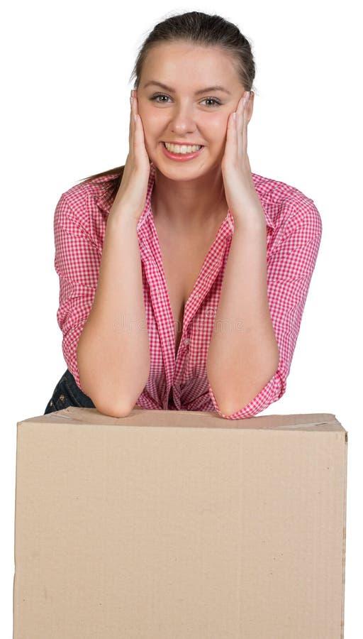 Mujer que descansa sus codos en la caja de cartón imagen de archivo