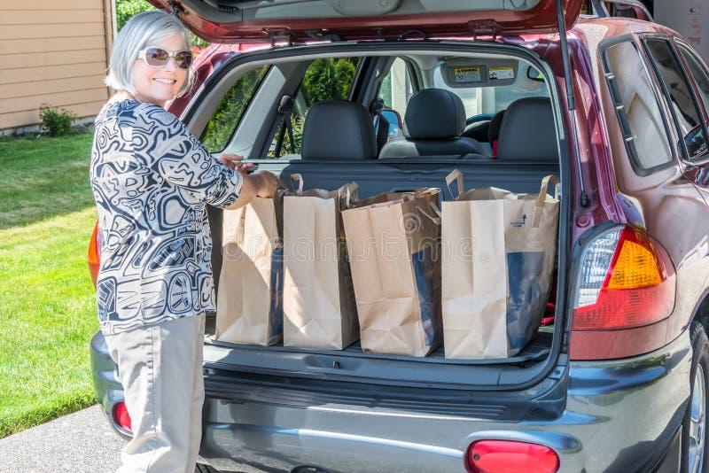 Mujer que descarga bolsos de ultramarinos del coche imagenes de archivo
