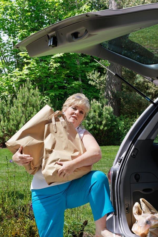 Mujer que descarga las tiendas de comestibles foto de archivo