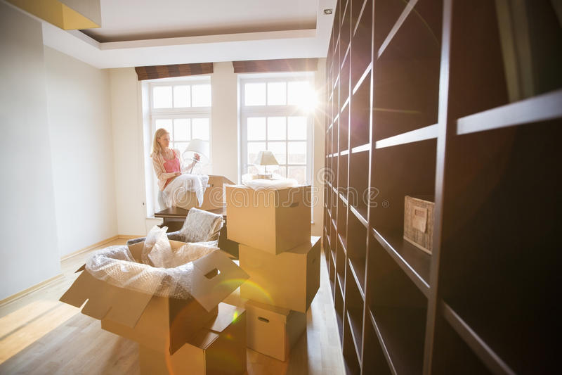 Mujer que desempaqueta la lámpara de la caja móvil en la nueva casa fotos de archivo libres de regalías