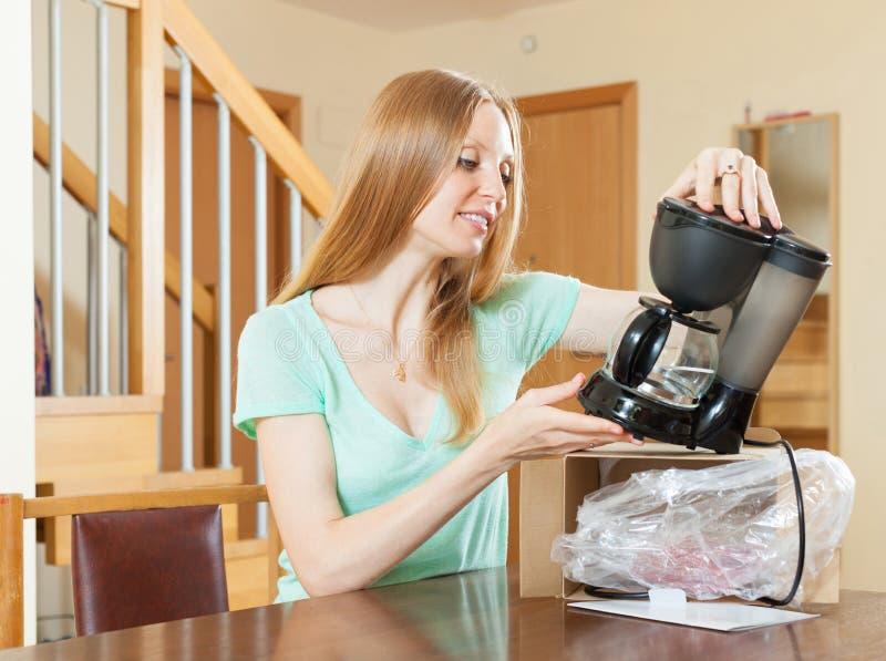 Mujer que desempaqueta y que lee el manual para la nueva cafetera en casa yo imágenes de archivo libres de regalías