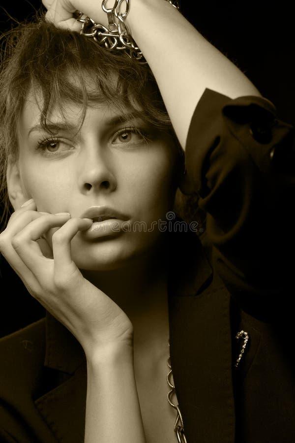 Mujer que desgasta la chaqueta negra con los encadenamientos imagenes de archivo