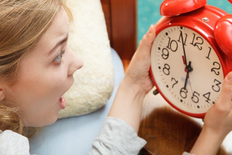 Mujer que despierta tarde apagando el despertador foto de archivo
